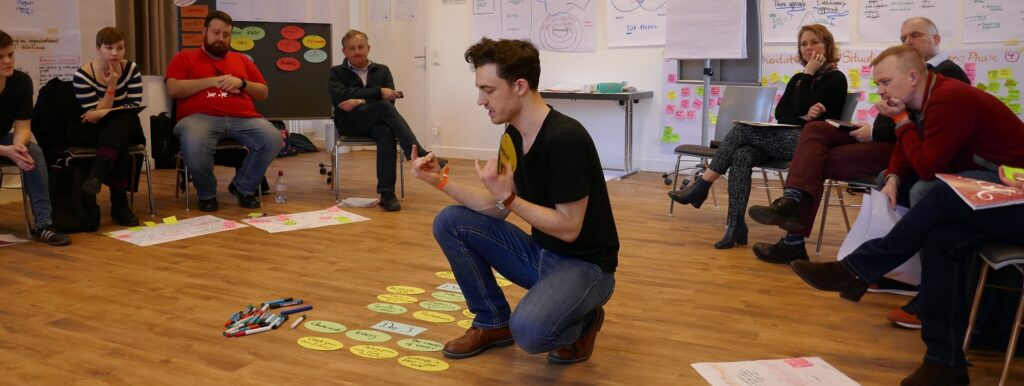 A man in the middle of a room with coloured pieces of paper on the floor, with people sat around watching